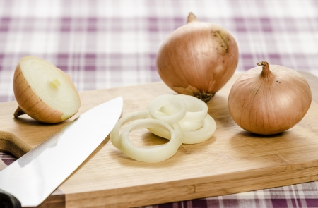 Onions and onionrings on cuttingboard with knife