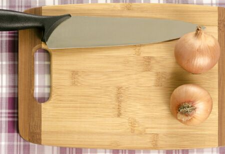 A cutting board with copy space  Framed with a knife and two onions