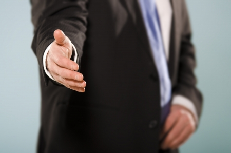 Middle section of suited man reaching hand towards the camera