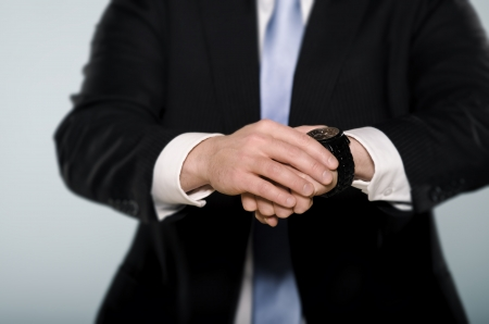 Middle section of a businessman wathcing his wrist watch