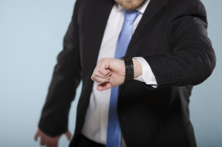 Middle section of casually suited man movin and checking time from his watch