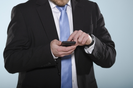 Middle section of casually suited man using a touch screen phone with his finger