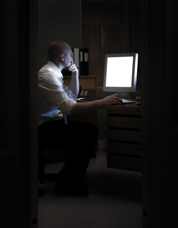 Late night office worker working overtime. White collar worker working on computer at night in dark office.