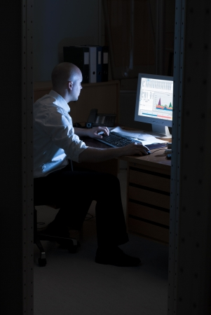 Late night office worker working overtime. White collar worker working on computer at night in dark office. photo