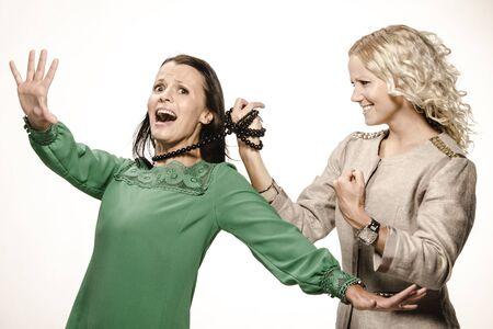 Blonde and brunette woman fighting  Friends having fun
