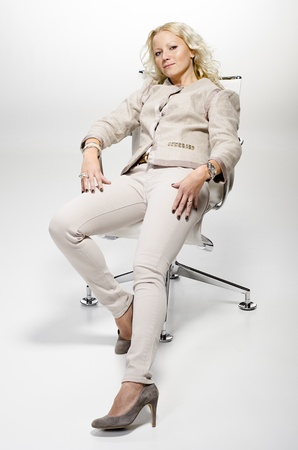 Casual and confident blond woman sitting on a office chair