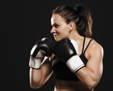 Beautiful muscular fitness woman wearing boxing gloves  Stock Photo