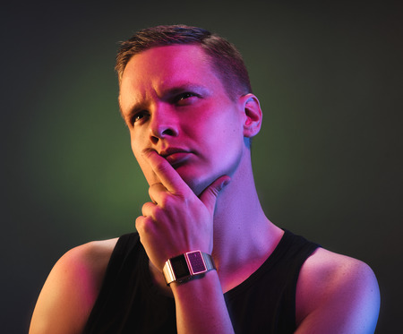 Hansome male model posing for camera waring tanktop and wrist watch.
