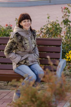 portrait of a beautiful happy old woman. Walks in autumn in the Park outdoors with a great mood, smiling, enjoying life. Looking at the camera. Happy old age, carelessness, leisure of elderly people Фото со стока