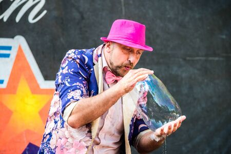 Volgodonsk, Russia-August 25, 2019: bubble show festival, art project ignite together. Young bright male actor on stage in a pink hat skillfully inflates large bubbles to the delight of children Editorial