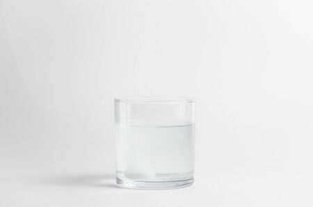 The effervescent tablet dissolves in a glass of water. Liquid medicine isolated on white background. Treatment of viral diseases. Help with depression and insomnia. Drink liquid multivitamins