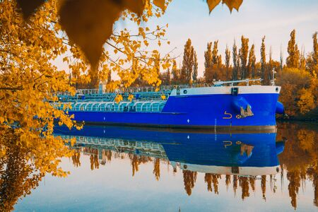 Beautiful autumn evening landscape. Colorful forest and ship quietly floating on the river. Blue barge on a background of Sunny leaves. Indian summer. Yellow trees in the rays of the departing sun