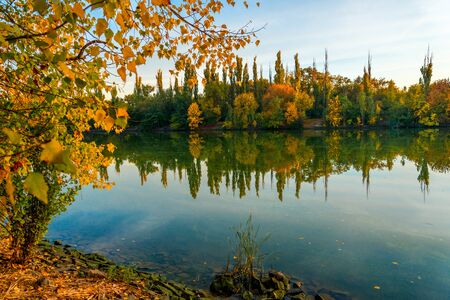 Beautiful autumn evening over a mountain river. Autumn landscape with colorful forest. Solar amber paysage. Indian summer landscape. Yellow trees in the rays of the departing sun. Autumn in Russia