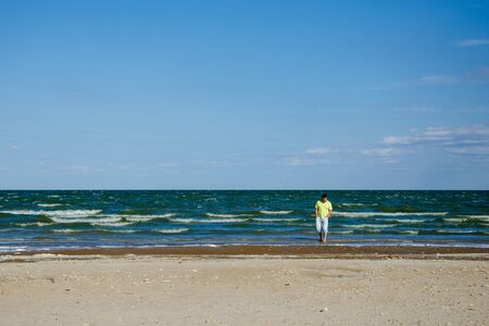 A lonely sad man walks along the seashore and longs. One wanders on a deserted summer beach and thinks about life. The concept of bad mood, depression, breakup of love relationships. Copy space