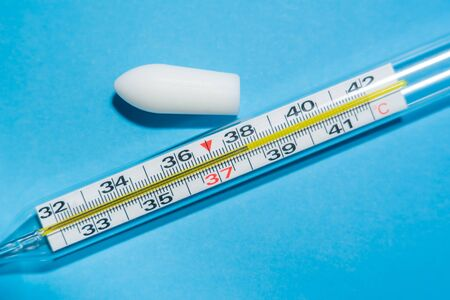 White suppository for anal or vaginal use on blue background and a thermometer with temperature of 38 degrees. Medical candles for treatment of Candida, thrush, hemorrhoids, inflammation and fever