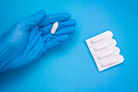 White suppository for anal or vaginal use in hand of a doctor wearing gloves on a blue background. Medical candles for treatment of Candida, thrush, hemorrhoids, inflammation and fever. Copy space Stock Photo