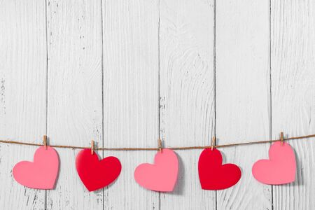 White painted wooden background with a garland of red and pink hearts. Natural rope and clothespins. Concept of recognition of love, romantic relationships, Valentines day in grunge style. Copy space