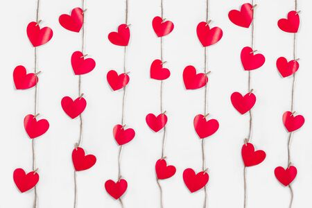 Garlands of red hearts on white isolated background. Romantic card. Natural rope and clothespins. The concept of recognition in love, romantic relationships, Valentine's Day. copy space