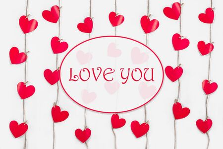 Garlands of red hearts on white isolated background. Romantic card with the text I love you. The concept of recognition in love, weddings, dates, Valentines Day