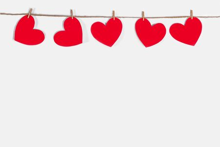Garland of red hearts on a white isolated background. Natural rope and clothespins. The concept of recognition in love, romantic relationships, Valentines Day. Copy space Stock fotó