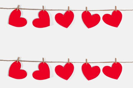 Garland of red hearts on a white isolated background. Natural rope and clothespins. The concept of recognition in love, romantic relationships, Valentines Day. Copy space