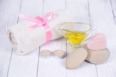 The concept of a Spa on Valentines Day. Candles, soap in the form of a heart with text I love you, stones, massage oil and a towel on a wooden background. Relaxation and wellness care. Bath procedure Standard-Bild