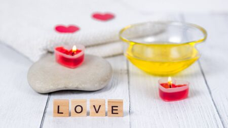 The concept of a Spa on Valentine's Day. Burn red heart-shaped candles, stones, massage oil, word love and white towel on a wooden background. Relaxation and wellness care. Bath procedure, cosmetology Standard-Bild
