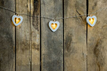 Old wooden background close-up with a garland of two white burning hearts. The concept of a Declaration of love, romantic relationships, Valentines day in grunge style. Copy space.