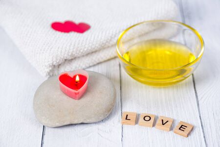 The concept of a Spa on Valentines Day. Burn red heart-shaped candles, stones, massage oil, word love and white towel on a wooden background. Relaxation and wellness care. Bath procedure, cosmetology Standard-Bild