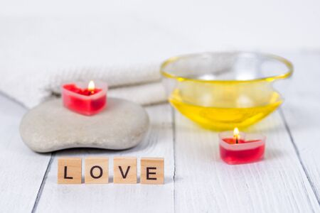The concept of a Spa on Valentines Day. Burn red heart-shaped candles, stones, massage oil, word love and white towel on a wooden background. Relaxation and wellness care.Bath procedure, cosmetology
