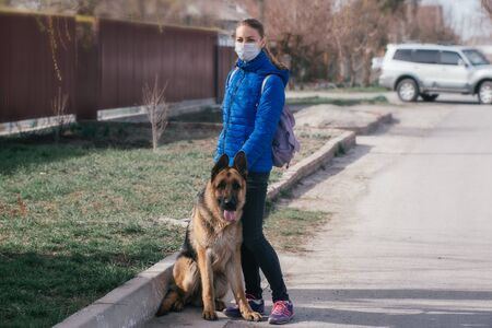 A girl in a protective medical mask walks a dog on the street. Leisure with a pet during quarantine. Walk with a German shepherd in the fresh air. Self-isolation and protection mode.