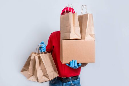 The concept of safe delivery. A courier in a red uniform and protective mask and gloves holds a large order, a cardboard box and many paper bags, contactless delivery of orders in quarantine. Standard-Bild