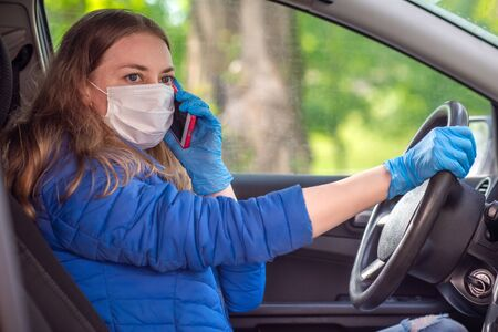 A woman driving a car in protective medical mask and gloves is talking on phone. Lifestyle and safe drive during a pandemic coronavirus. Protect driver and passengers. New normal and modern reality.