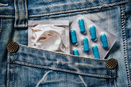 A pack of blue capsules in your pants pocket and a condom. Pills for mens health and sexual energy in jeans. Concept of erection, potency. Treatment of male infertility, impotence and prostatitis.