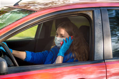 A woman driving a car in protective medical mask and gloves is talking on phone. Lifestyle and safe drive during a pandemic coronavirus. Protect driver and passengers. New normal and modern reality Stock Photo