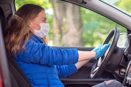 A woman driving car in a protective medical mask and gloves honks in emergency. Lifestyle and safe drive during a pandemic coronavirus. Protect driver and passengers. New normal and modern reality. Stock Photo