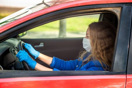 A woman driving a car in a protective medical mask and gloves. Lifestyle and safe drive during a pandemic coronavirus in quarantine. Protect the driver and passengers. New normal and modern reality.