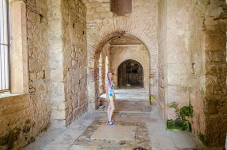 Caucasian Girl tourist during the tour walking in the walls of Ancient Byzantine Church of St. Nicholas Wonderworker, Santa Claus. Old Greek antique temple in city of Demre, Antalya, Turkey