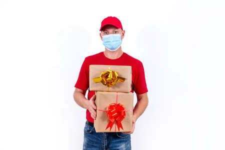 Safe contactless remote delivery of holiday gifts during the coronavirus pandemic. A courier in a red uniform and protective medical mask holds two beautiful gift boxes with bows.