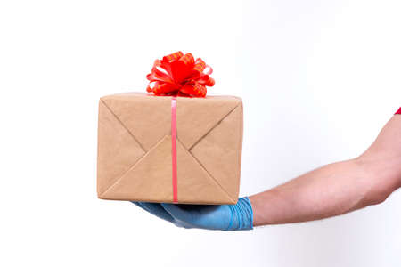 Safe contactless remote delivery of holiday gifts during the coronavirus pandemic. Close up. Courier hand in protective medical gloves holds a beautiful gift box with a bow on a white background. 免版税图像