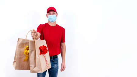 Banner. Safe contactless remote delivery of holiday gifts during coronavirus pandemic. A courier in red uniform and protective medical mask holds two beautiful gift paper bags with bows. Copy space. 免版税图像
