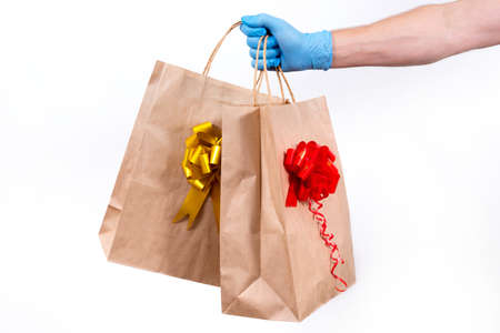 Secure contactless remote delivery of holiday gifts during the coronavirus pandemic. Close up. A courier hand in protective medical gloves holds two paper gift bag with a bow on a white background. 免版税图像