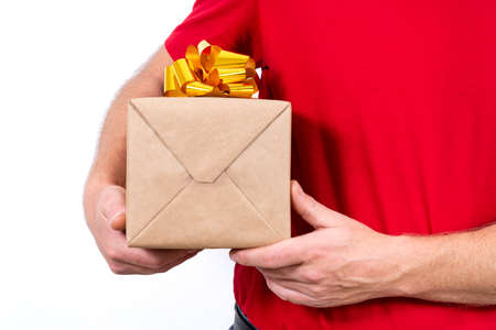 Safe contactless remote delivery of holiday gifts during the coronavirus pandemic. Close up. Courier hand holds a beautiful gift box with a bow. Copy space.