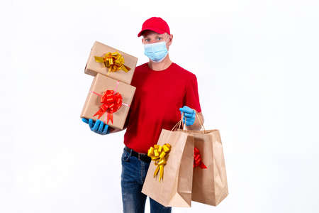 Safe contactless remote delivery of holiday gifts during coronavirus pandemic. A courier in red uniform and protective medical mask and gloves holds large order, many gift boxes and bags with bows.