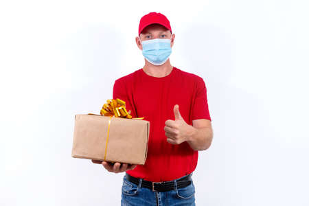 Safe delivery of gifts for holidays. A courier in red uniform and protective medical mask holds box with a bow. Contactless remote gift orders in quarantine during the coronavirus pandemic.