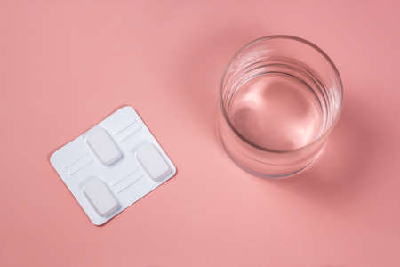 White vaginal antibacterial pills on pink