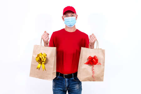 Safe contactless remote delivery of holiday gifts during coronavirus pandemic. A courier in red uniform and protective medical mask holds two beautiful gift paper bags with bows on white background.