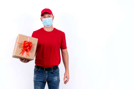 Safe delivery of gifts for holidays. A courier in red uniform and protective medical mask holds box with a bow. Contactless remote gift orders during pandemic. Banner with space for text. Copy space.