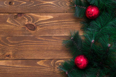 Wooden background with a decorated Christmas tree branch with space for text. New Year concept. Copy space. The surface of the table to shoot flat lay. Top view. Natural raw planed wood. Stok Fotoğraf
