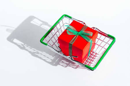 Grocery basket with red gift box on white isolated background. Christmas shopping online. Copy space. Holiday sales and discounts on new year and black Friday. Trading business. Space for text.